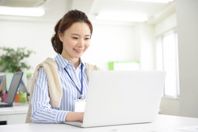 ノートパソコンで仕事をする女性社員のイメージ画像